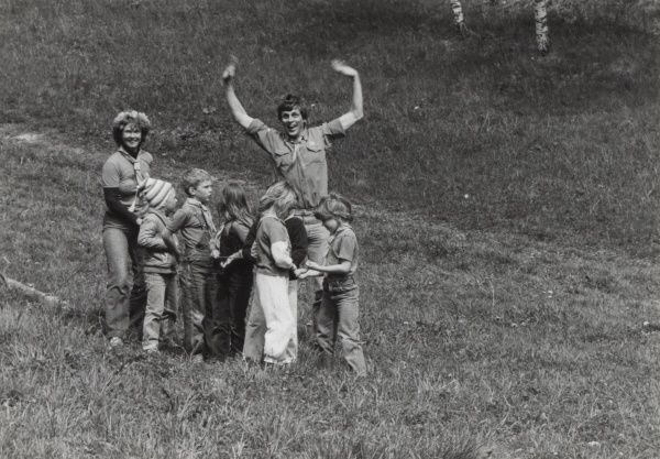 Swedish Beaver Scouts and leaders playing a game. One of the leaders waves at the camera.  circa 1892
