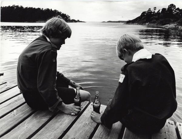 Two Swedish boy scouts dangle their feet in to the water of a lake off a jetty, as they enjoy a refreshing bottle of Coca Cola. circa 1980s