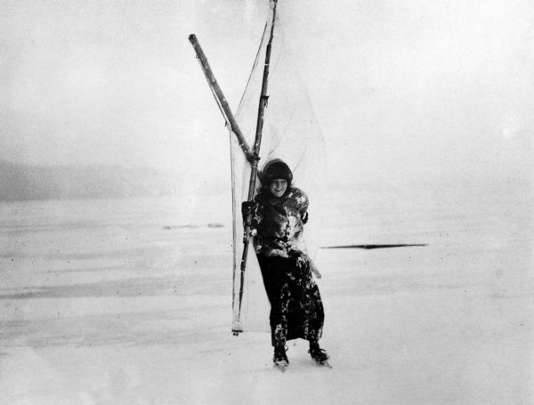 A happy young woman ice yachting (or sail skating) on a frozen lake in Sweden. Date: 1930s