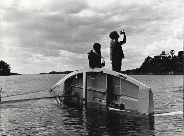Two Swedish Scouts awaiting rescue from their overturned light sailing boat enjoy a refreshing bottle of pop in the middle of the lake. They appear to be standing on a platform created by the elevated the keel. circa 1980s