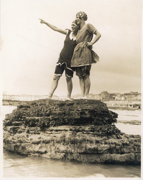 Two girls stand on a seaweed- covered rock at low tide at Hastings, showing off their two-piece bathing costumes which consist of shorts or bloomers & tunics