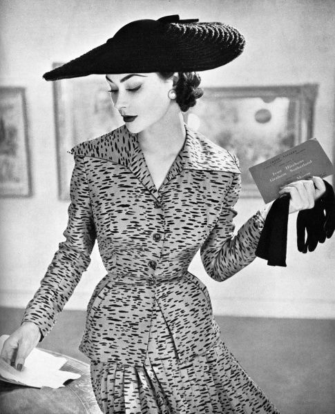 A model at an art exhibition wearing a skirt suit of pure silk shantung in a coffee colour splashed with black by Marcus. It has a pleated skirt and a pretty wide-collared neckline. Date: 1953