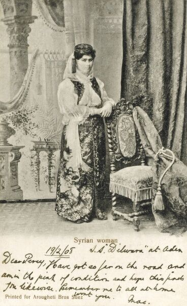 A opulent studio shot of an exotic Syrian Woman, in a fine dressed and wearing a veil. Date: 1908