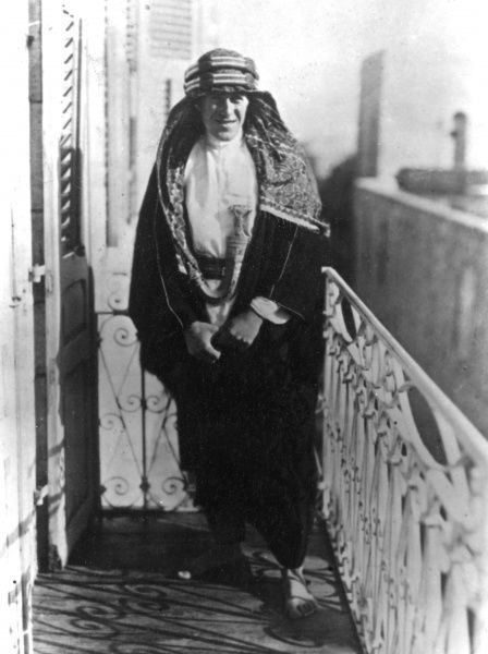 Lieutenant Colonel Thomas Edward Lawrence (aka Lawrence of Arabia, 1888-1935), British Army officer best known for his liaison role during the Arab Revolt against Ottoman Turkish rule of 1916-1918. Seen here in Arab costume, standing on a balcony