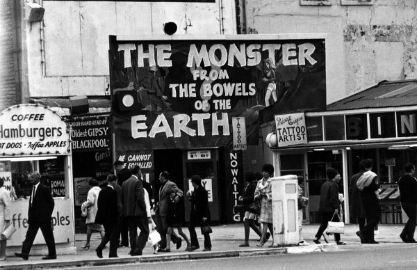 'The Monster from the Bowels of the Earth', one of the attractions on offer, along with palm reading, hamburgers, tattooing, on the Golden Mile, Blackpool, Lancashire, England Date: late 1960s