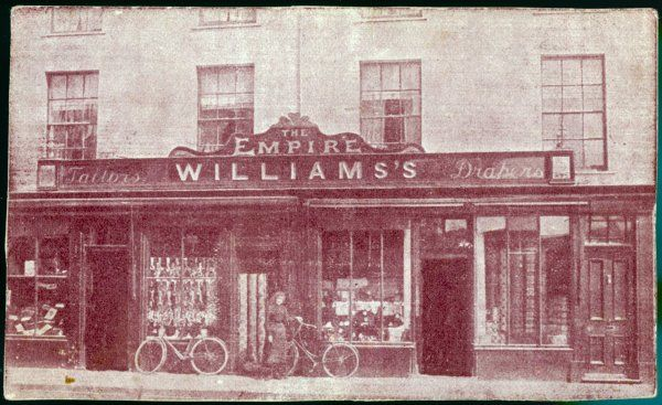 A girl leans her bicycle against the window of 'THE EMPIRE' - Williams, Tailors and drapers. But where this is, we do not know