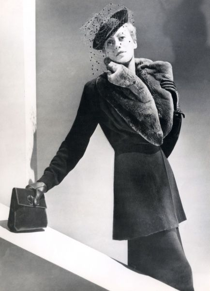 A tailor-made costume with long-line jacket with a luxurious collar of clipped beaver, a small hat & veil worn on one side & an elegant clutch bag. Date: 1930s
