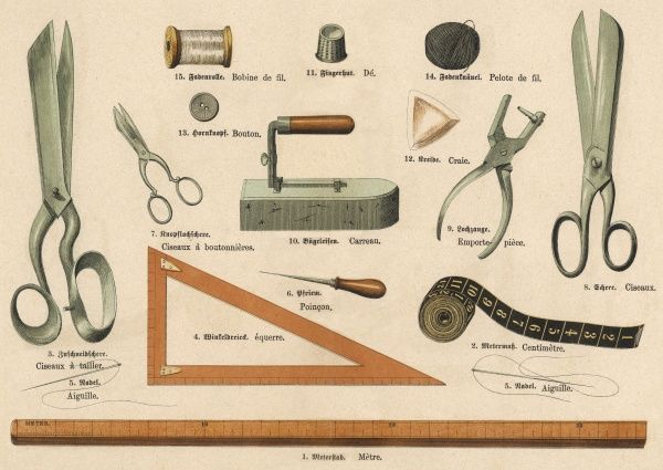 Tools used in tailoring, including scissors, needle and thread, chalk, measuring tape, a ruler and a smoothing iron