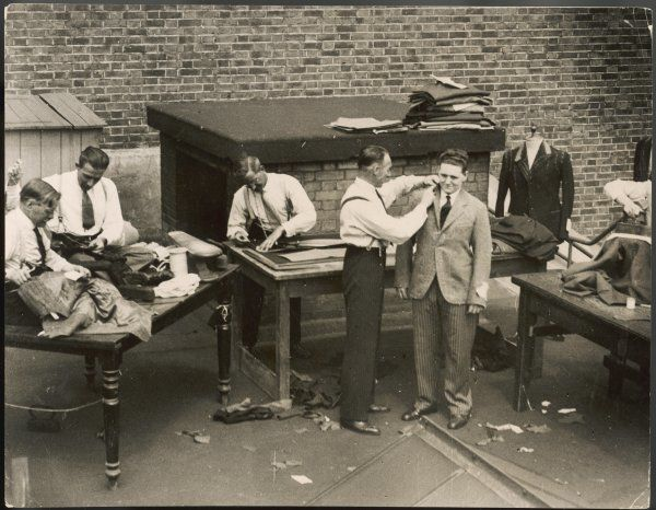 Tailors working on a roof during a heat wave: measuring a suit for a customer, cutting and sewing cloth, Regent Street, London, England