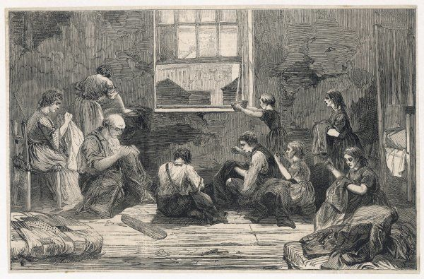A group of men, women and children work as tailors in a slum apartment. They sit on the floor of a very bare room to sew