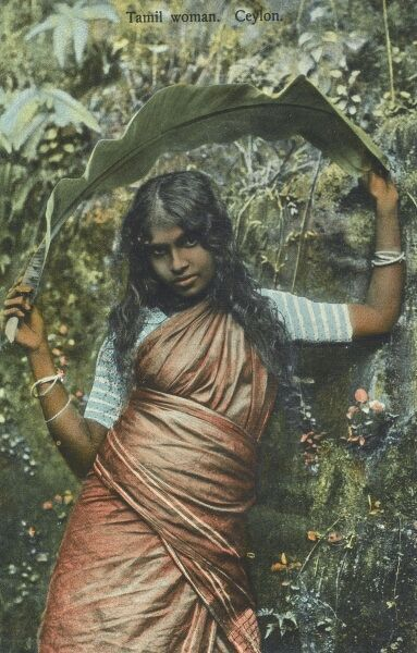 A Tamil Woman from Sri Lanka holding a large banana leaf above her head Date: circa 1920s