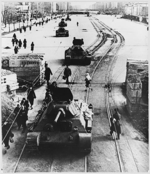 Tanks advance to battle positions along a city street