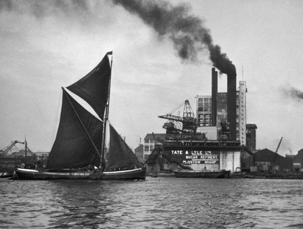 A coastal barge sailing by the famous Tate and Lyle sugar refinery works, Plaistow Wharf, off Silvertown, North Woolwich, east London