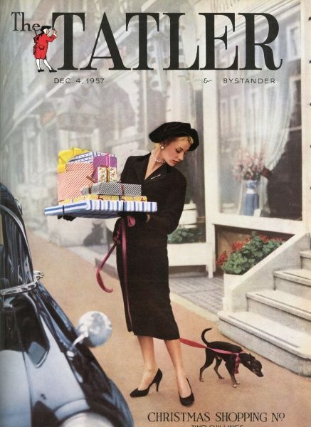 An elegant woman in a fitted black skirt suit and matching hat seems to have become rather tangled with her roy dog as she balances a huge pile of Christmas presents before getting into a taxi on a London street
