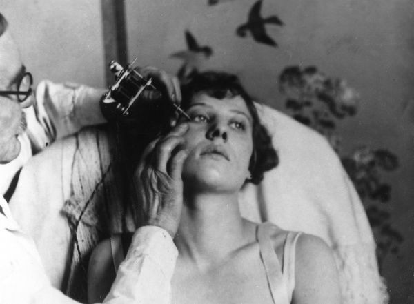 The latest craze for feminine beauty is the tattooing of eyelids with small flowers and butterflies. This picture shows a lady being tattooed in a West End (of London) salon. Date: 1929