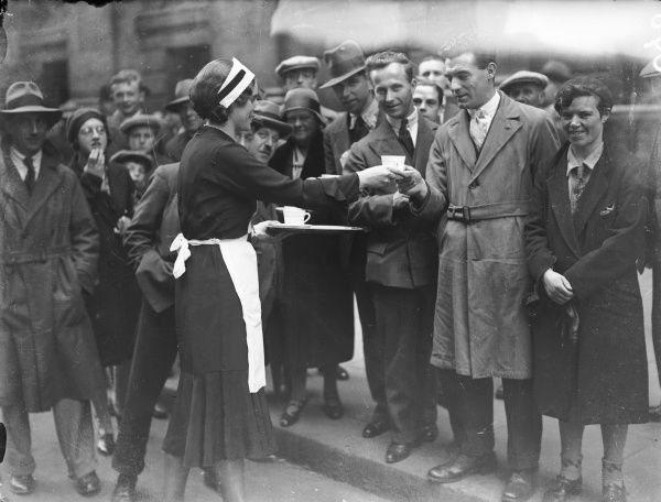 A kind tea lady hands out cups of hot tea to a crowd of people waiting outside No. 10 Downing Street, London, the official residence of the British Prime Minister of the day