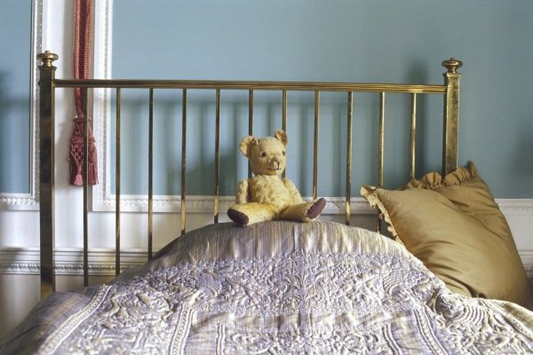A lovely old Edwardian teddy bear takes pride of place on a little boy's brass bed