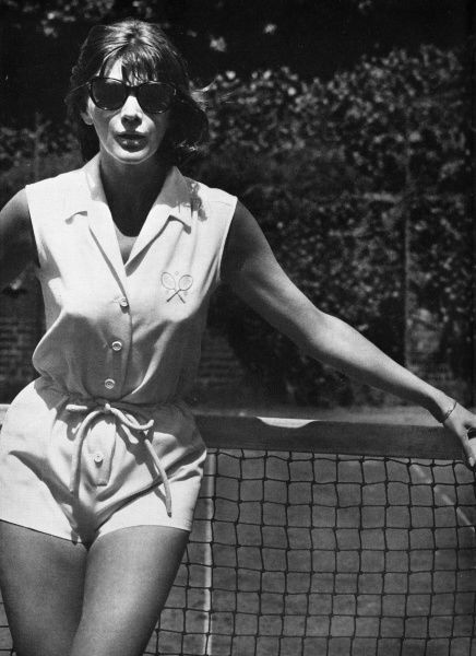 A tailored tennis suit in cotton pique with a drawstring waist and crossed racquets motif embroidered in blue on the shirt top designed by tennis fashion guru, Teddy Tinling. Date: 1962
