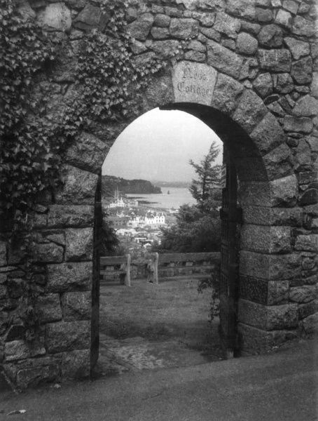 A distant glimpse of Teignmouth, Devonshire,, England, seen through the entrance to the Botanical Gardens at Shaldon. Date: early 1960s