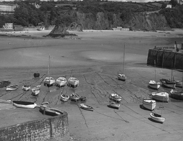Beached boats at Tenby Bay, Pembrokeshire, Wales. Date: 1950s