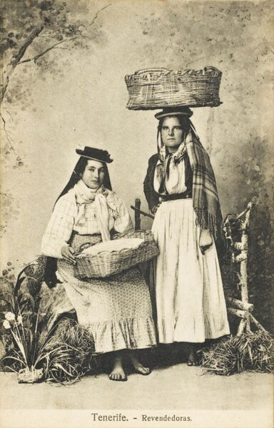 Two women in traditional costume on the Island of Tenerife. The card caption translates as 're-sellers' - these ladies are likely to be itinerant traders of goods of some description. They carry their baskets on flattened rounded hats