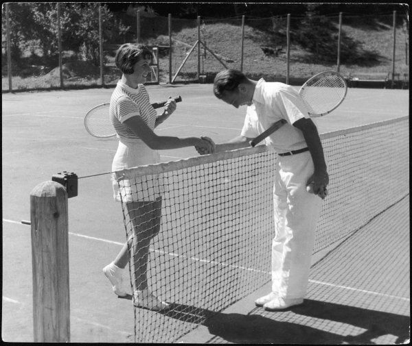 A chivalrous gentleman tennis player bows as he shakes the hand of his attractive female opponent over the net!