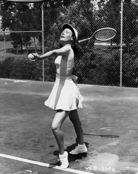 A fashionable young woman strikes a pose as she attempts to serve, during a game of tennis. Date: 1940s