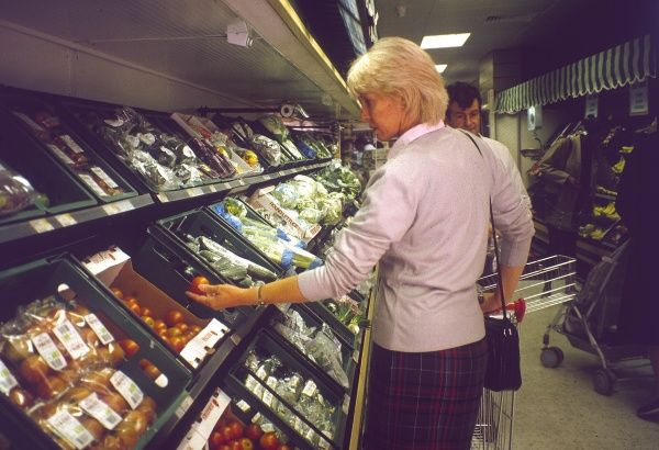 A housewife browses through the pre-packed fruit and vegetable counter at Tesco's supermarket, London. Date: 1991