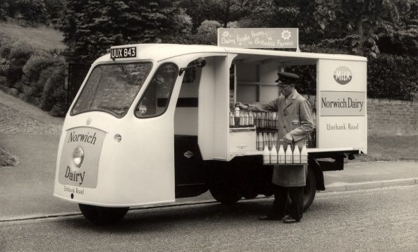 A Milkman on his morning round, fills up a crate from his vintage yet stylish three-wheeled float. This model is a Norwich Dairy milk electric, (DP Kathanode battery operated) delivery float