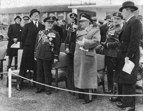 Marshal Tito firing the Verey starting pistol to begin the RAF Air display at Duxford. On the left, in the bowler hat, is Lord De L'Isle and Dudley, V.C, and on the extreme right is Duncan Sandys, Minister of Supply