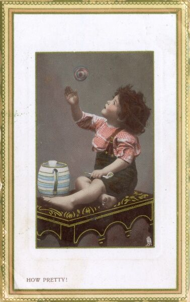 A young toddler sat atop a padded stool playing with a large bubble, that he has blown through a pipe Date: circa 1906