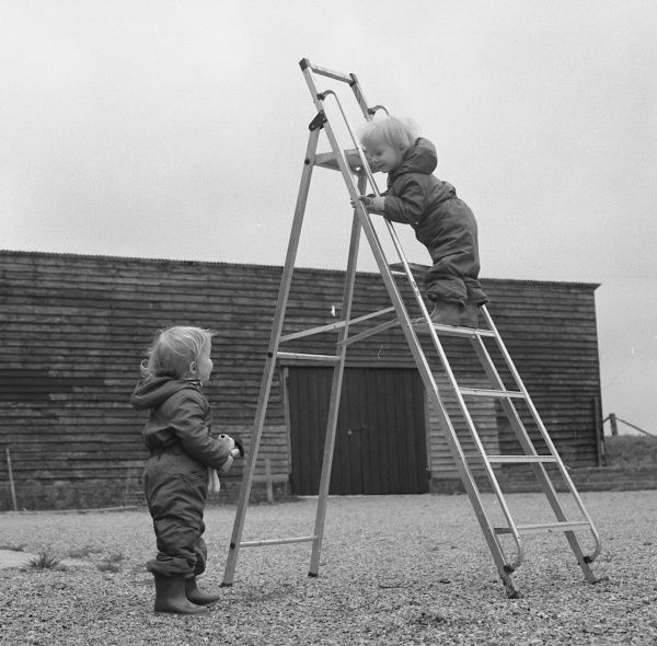 Two toddlers playing with a step ladder on a gravelled area in front of a farm building