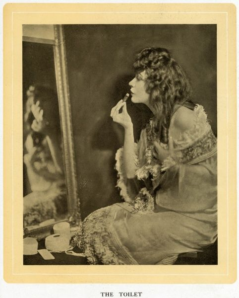 A photographic study of the film actress Renee Adore, seen applying lipstick to her pursed lips as she looks in a mirror