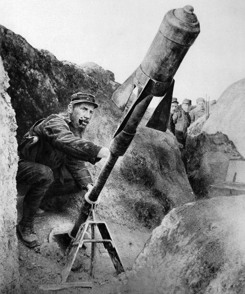 A French soldier about to fire a torpedo-shell from a trench-gun. The winged shell kept a straight course and exploded laterally, causing widespread damage to its target
