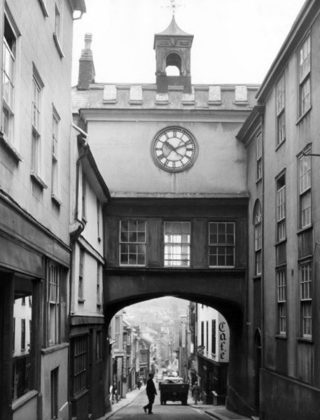 Looking down Fore Street, the main street of Totnes, Devon and the splendid East Gate Arch, with its distinctive clock tower. Date: 1950s