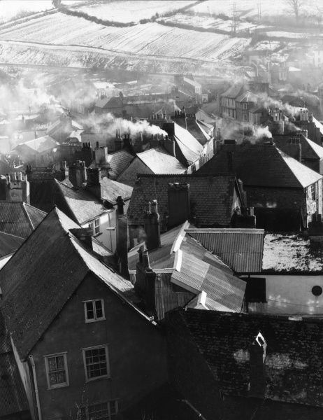 Winter view of Totnes, Devon, England, seen from the castle walls. The houses (note the coal smoke coming from the chimneys) in this view line the town's main street. Date: 1950s