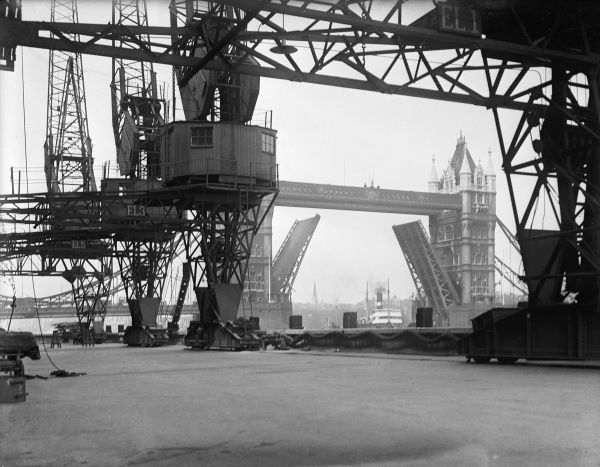 A view of Tower Bridge, a bascule bridge, open to allow ships to sail down the Thames. Industrial view from beneath massive cranes