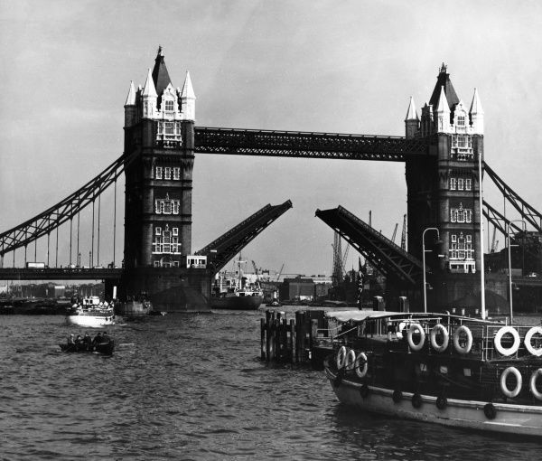 Tourist vessels such as 'Skylark London' and other ships, passing under Tower Bridge, a bascule bridge which has been raised to let them sail through on the Thames. Date: 1950s