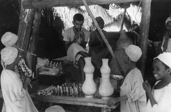 In one of the bazaars of the city of Muscat, Oman, Middle East, stands a solitary toy stall, selling reed pipes and gaudily painted wooden dolls. Date: 1930s