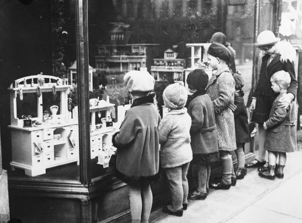 Mothers and children admiring all the latest toys for sale in a toy shop window display