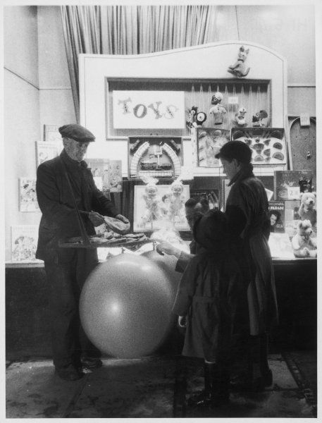A father kneels down beside his daughter to explain that the small deflated balloon will inflate into a giant balloon, just like the one on display at this toy stall