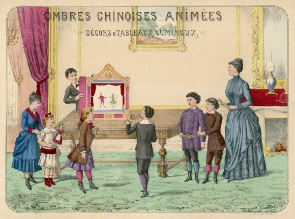 A boy demonstrates a toy theatre to his brothers, sisters and mother