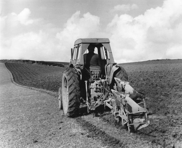 A Devon farmer in the process of ploughing his field into neat furrows using a tractor- driven plough