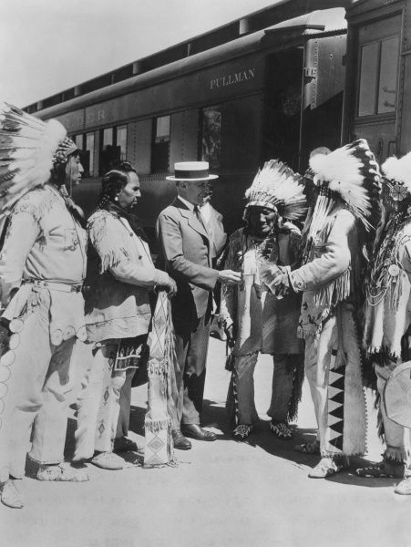 Native American Indians trading goods on the platform of a train station for a bottle of liquor from a gentlman in a straw boater, U.S.A. Date: early 1930s