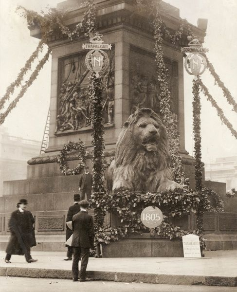 View of one of the lions at the foot of Nelson's Column in Trafalgar Square, Central London, at the time of the Nelson Centenary Celebrations, with decorations commemorating the Battles of Copenhagen and Trafalgar