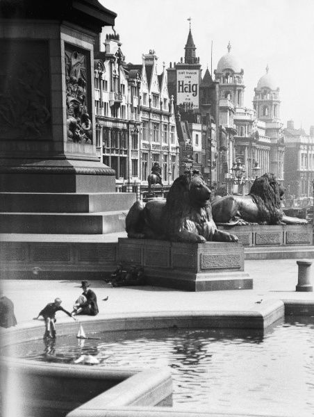 A boy sailing a boat in one of a fountain, overshadowed by two of the four bronze lions sculpted by Sir Edwin Landseer, Trafalgar Square, London