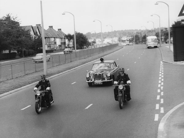 A Metropolitan Police Traffic Accident Group, consisting of two Triumph motorcycles and one Wolseley 6/110 motor car, fitted with radio transmitter and loudspeaker. They are making their way along a dual carriageway somewhere in the London suburbs