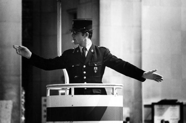 A Gendarme controlling the traffic, Paris, France. Date: late 1960s