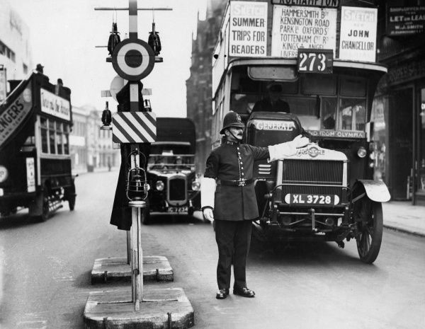 A policeman uses hand signals to stop the 273 bus to Roehampton, London. Date: 1930