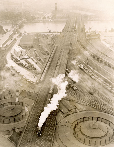 A view from the top of the gasometer at Battersea showing the junction of railway lines outside Victoria Station and the river Thames on the left below Chelsea Bridge